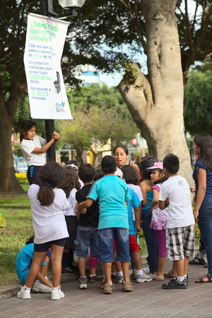 LIMA, PERU - MARCH 21, 2012: Unidentified adults and children in the Kennedy Park in the district of Miraflores on March 21, 2012 in Lima, Peru. A woman and many children are standing at a sign informing about wasting water through malfunctioning toilets  Editorial