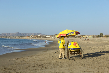 ice cream cart: LOS ORGANOS, PERU - AUGUST 30, 2013: Unidentified person selling ice cream in a cart on the sandy beach on August 30, 2013 in Los Organos, Peru. Los Organos is a small town in Northern Peru, close to the touristy beach town of Mancora.