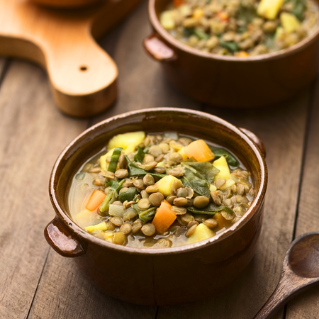 Vegetarian soup made of lentils, spinach, potato, carrot and onion served in dark brown bowls (Selective Focus, Focus one third into the soup) Stockfoto