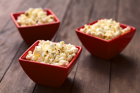 popped: Three red bowls of freshly prepared salted popcorn  Selective Focus, Focus one third into the popcorn in the first bowl