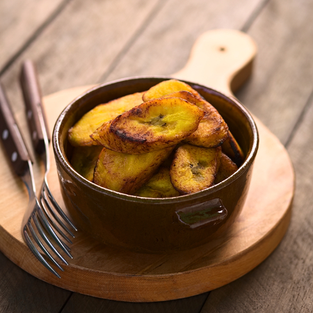 plantain: Fried slices of the ripe plantain in bowl, which can be eaten as snack or is used to accompany dishes in some South American countries  Selective Focus, Focus on the front of the upper plantain slice  Stock Photo
