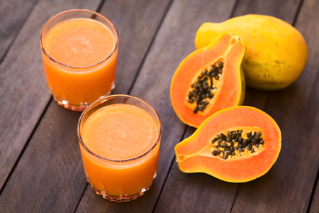 Two glasses of freshly prepared papaya juice with papaya fruits on the side  Selective Focus, Focus into the middle of the first juice