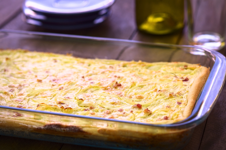 glass topped: Traditional German Zwiebelkuchen or onion cake, made of a yeast dough and topped with onions and bacon in cream sauce in a glass baking pan  Very Shallow Depth of Field, Focus one third into the image