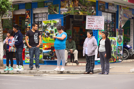 touristy: BANOS, ECUADOR - FEBRUARY 22, 2014: Unidentified people on the corner of the streets Oriente and Pedro Vicente Maldonado with the Siseaventours Travel Agency in the back on February 22, 2014 in Banos, Ecuador. Banos is a small touristy town which is mainl