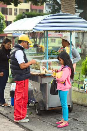 mote: BANOS, ECUADOR - FEBRUARY 22, 2014: Unidentified people eating at snack stand selling roasted pork skin with beans (mote), tomato, onion, lime and corn at the Sebastian Acosta Park on February 22, 2014 in Banos, Ecuador. Editorial