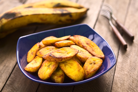 Fried slices of the ripe plantain in blue bowl, which can be eaten as snack or is used to accompany dishes in some South American countries, ripe plantains in the back.  Selective Focus, Focus on the front of the upper plantain slice