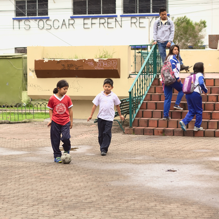freetime activity: BANOS, ECUADOR - FEBRUARY 25, 2014  Unidentified children playing football in Sebastian Acosta Park on February 25, 2014 in Banos, Ecuador