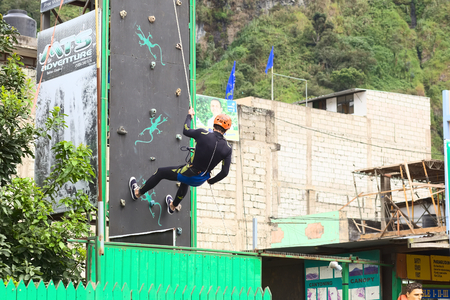 freetime activity: BANOS, ECUADOR - FEBRUARY 25, 2014  Unidentified person practicing abseiling for canyoning on a climbing wall on February 25, 2014 in Banos, Ecuador  Banos is a small touristy town offering a lot of outdoor activities, such as canyoning  abseiling a water