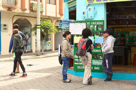 tour operator: BANOS, ECUADOR - FEBRUARY 25, 2014: Unidentified people in front of the tour operator Tungurahua Explorer on the corner of the streets 16 de Diciembre and Vicente Rocafuerte on February 25, 2014 in Banos, Ecuador. Banos is a small touristy town, mainly vi