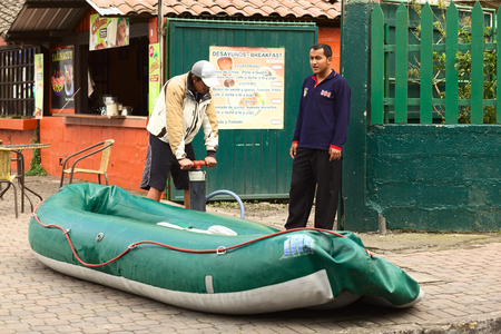 inflate boat: BANOS, ECUADOR - FEBRUARY 25, 2014: Unidentified people inflating a rubber boat on 16 de Diciembre Street on February 25, 2014 in Banos, Ecuador. Banos is known and visited for its various outdoor activities, such as rafting, canyoning, bridge jumping, et