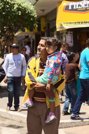 onlooker: BANOS, ECUADOR - MARCH 2, 2014  Unidentified man and girl watching the carnival parade on Ambato Street on March 2, 2014 in Banos, Ecuador
