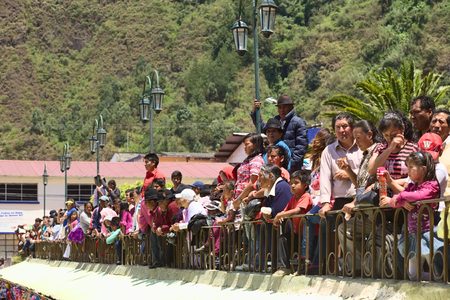 onlooker: BANOS, ECUADOR - MARCH 2, 2014  Unidentified people watching the carnival parade on Ambato Street at Sebastian Acosta Park on March 2, 2014 in Banos, Ecuador