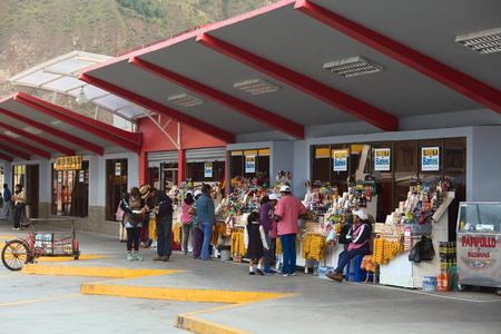 two people with others: BANOS, ECUADOR - MARCH 7, 2014  Unidentified people at the bus terminal on March 7, 2014 in Banos, Ecuador  Two people are looking at a map and others are around the numerous snack stands offering sweets, fruits and drinks  Editorial