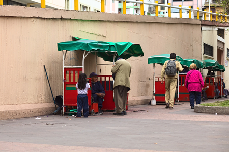 AMBATO, ECUADOR - APRIL 9, 2014: Unidentified people at shoe cleaning booths in 12 de Noviembre Park on April 9, 2014 in Ambato, Ecuador. Ambato is the capital of the Tungurahua Province in Central Ecuador.