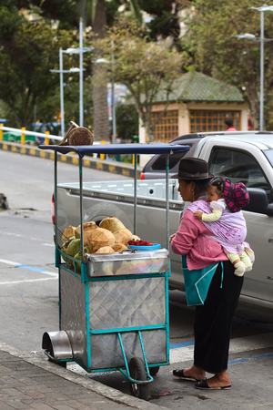 martinez: AMBATO, ECUADOR - APRIL 9, 2014: Unidentified woman with baby at a small cart filled with coconut at the roadside on Martinez Street on April 9, 2014 in Ambato, Ecuador. Ambato is the capital of the Tungurahua Province in Central Ecuador.