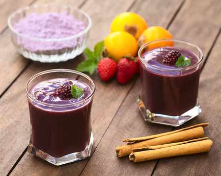 panela: Ecuadorian traditional thick drink called Colada Morada, prepared by cooking purple corn flour and different fuits  and seasoned with panela, cinnamon, allspice and cloves  Stock Photo