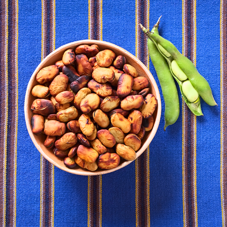 haba: Toasted fava beans (lat. Vicia faba, South America: haba) eaten as snack in Bolivia, served in clay bowl with fresh green fava beans on the side, photographed with natural light (Selective Focus, Focus on the toasted beans) Stock Photo