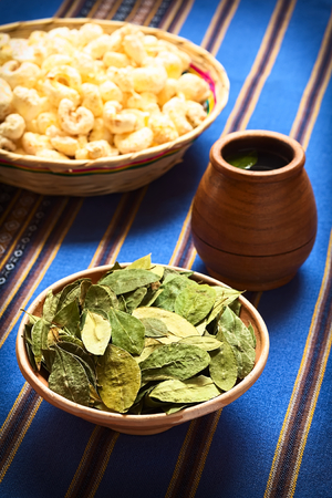 mate infusion: Dried coca leaves in clay bowl with fresh coca tea (mate de coca) and Bolivian snack called Pasancalla (popped corn) in the back, photographed with natural light (Selective Focus, Focus on the middle of the coca leaves)