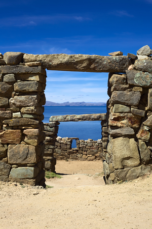 reachable: View through a door frame of the Chinkana archeological site of Tiwanaku (Tiahuanaco) origin on the Northwestern part of the Isla del Sol (Island of the Sun) in Lake Titicaca in Bolivia. Isla del Sol is a popular tourist destination and is reachable by bo