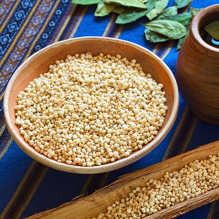 bolivian: Bolivian popped quinoa cereal in small clay bowl with coca tea on the side, photographed with natural light (Selective Focus, Focus on the front of the popped quinoa in the bowl)