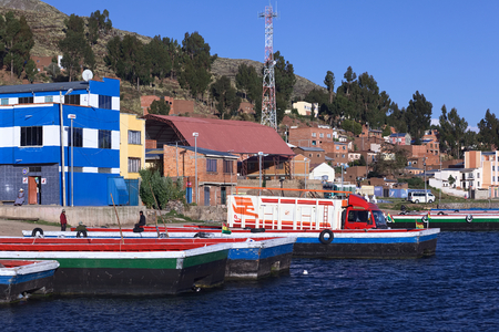 pablo: TIQUINA, BOLIVIA - OCTOBER 16, 2014: Truck on wooden ferry waiting to be transported over the Strait of Tiquina at Lake Titicaca on October 16, 2014 in San Pablo de Tiquina, Bolivia