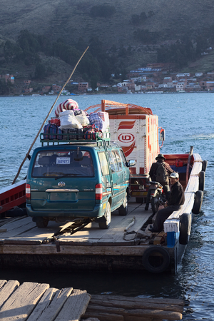 pablo: TIQUINA, BOLIVIA - OCTOBER 16, 2014: Wooden ferry loaded with truck, minibus and motorbike leaving one side of the Strait of Tiquina at Lake Titicaca on October 16, 2014 in San Pablo de Tiquina, Bolivia Editorial