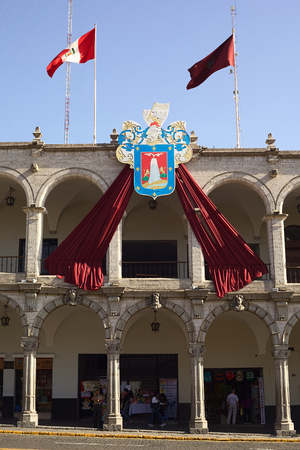 AREQUIPA, PERU - AUGUST 22, 2014: The city hall on Plaza de Armas (main square) with the coat of arms and red flag of Arequipa and the Peruvian banner on August 22, 2014 in Arequipa, Peru. The city center of Arequipa is UNESCO World Cultural Heritage Site