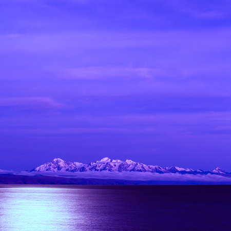 Lake Titicaca and the snow-capped mountains of the Andes photographed from the Isla del Sol (Island of the Sun) at night with the full moon shining photo