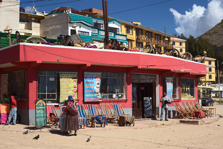 COPACABANA, BOLIVIA - OCTOBER 19, 2014: Unidentified people standing in front of the resto bar Flor de Mi Tierra on the corner of the avenues 6 de Agosto and Costanera along the shore of Lake Titicaca in the small tourist town on October 19, 2014 in Copac