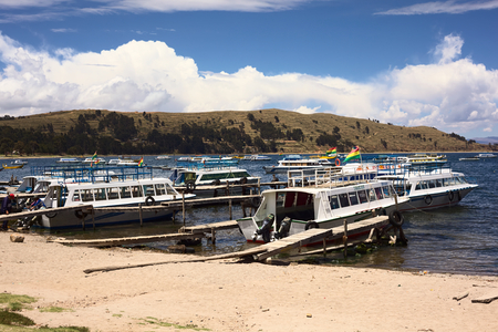 tour boats: COPACABANA, BOLIVIA - OCTOBER 28, 2014: Many tour boats in the harbor of the small tourist town of Copacabana in a bay of Lake Titicaca on October 28, 2014 in Copacabana, Bolivia. Boats to the popular travel destination of Isla del Sol go from here daily.