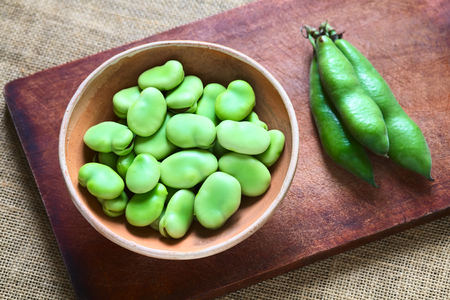 Raw broad beans (lat. Vicia faba) in bowl with pods on the side, photographed with natural light  Banque d'images