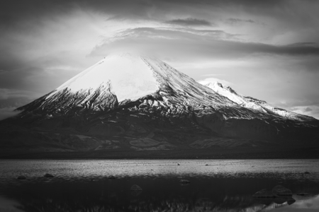 stratovolcano: Parinacota stratovolcano (6348 meters) and Chungara Lake on the border of Chile and Bolivia on the way from La Paz to Arica. Parinacota is part of the Payachata volcanic group in Northern Chile. (Monochrome Image) Stock Photo