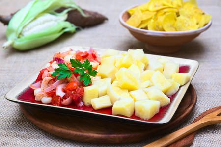 Cooked cassava or manioc with a cooked vegetable mix of onion, Peruvian or Cuzco corn and tomato photographed with natural light (Selective Focus, Focus on the parsley leaf) photo