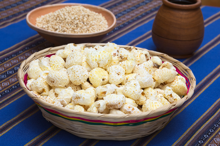 popped: Sweetened popped white corn called Pasancalla eaten as snack in Bolivia served in a woven basket with coca tea in the back, photographed with natural light (Selective Focus, Focus in the middle of the snack) Stock Photo