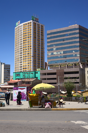 administrative buildings: LA PAZ, BOLIVIA - OCTOBER 12, 2014: Unidentified street vender along the Camacho avenue with tall modern buildings in the back in the administrative capital on October 12, 2014 in La Paz, Bolivia