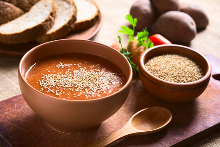 potato soup: Cream of vegatable soup made of tomato, carrot, potato and parsley served in bowl and sprinkled with sesame seeds, photographed with natural light (Selective Focus, Focus in the middle of the soup)