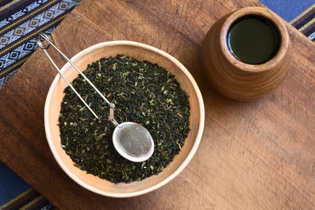 tea strainer: Overhead shot of dried green tea leaves in bowl with a tea strainer on top and wooden tea cup on the side photographed with natural light