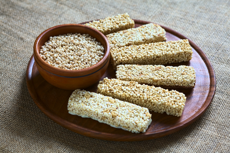 popped: Popped quinoa seeds in bowl with quinoa cereal bars, one with honey the other mixed with amaranth, on wooden plate photographed with natural light (Selective Focus, Focus into the middle of the popped quinoa seeds) Stock Photo