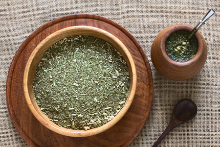 yerba mate: Compañero sudamericano yerba (yerba mate) hojas secas en un tazón de madera con una taza compañero de madera y bombilla (paja) llena de té junto a él fotografiada con luz natural. El mate es la infusión nacional de Argentina. (Enfoque selectivo, enfoque en el té de l seca