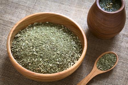yerba mate: Compañero sudamericano yerba (yerba mate) hojas secas en un tazón de madera con una taza gemela de madera llena de té junto a él fotografiada con luz natural. El mate es la infusión nacional de Argentina. (Enfoque selectivo, centrarse en el medio de las hojas de té secas)