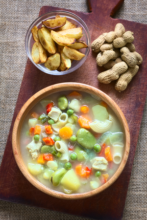 broad bean: Overhead shot of Bolivian traditional Sopa de Mani (peanut soup) made of meat, pasta, vegetables (pea, carrot, potato, broad bean, pepper, corn) with ground peanut in wooden bowl, traditionally served with fried potatoes, photographed with natural light (