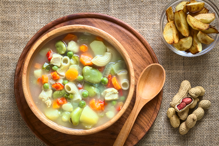 Overhead shot of Bolivian traditional Sopa de Mani (peanut soup) made of meat, pasta, vegetables (pea, carrot, potato, broad bean, pepper, corn) with ground peanut in wooden bowl, traditionally served with fried potatoes, photographed with natural light