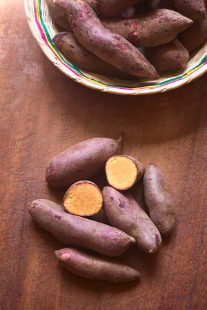 batata: Tiro de arriba de batata cruda morado (lat. Ipomoea batatas) sobre tabla de madera fotografiado con luz natural