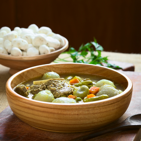 haba: Bolivian traditional soup called Chairo de Tunta (tunta is a freeze-dried potato typical in the Andean regions) made of tunta, beef, broad beans, peas and carrots, uncooked tunta in the back, photographed with natural light (Selective Focus, Focus in the