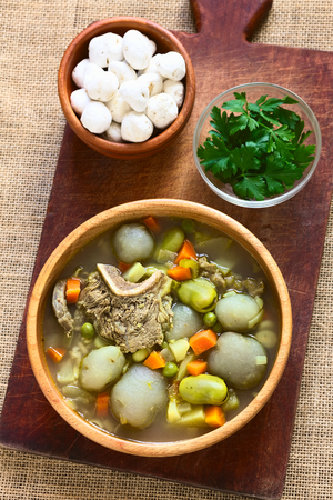 haba: Bolivian traditional soup called Chairo de Tunta (tunta is a freeze-dried potato typical in the Andean regions) made of tunta, beef, broad beans, peas and carrots, uncooked tunta in the back, photographed with natural light (Selective Focus, Focus on the  Stock Photo
