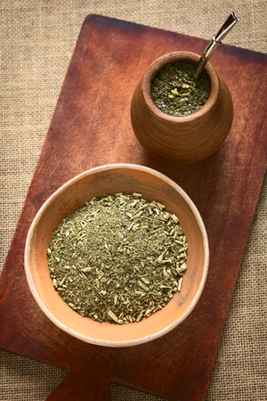 South American yerba mate (mate tea) dried leaves in clay bowl with a wooden mate cup filled with tea photographed with natural light. Mate is the national infusion of Argentina. photo