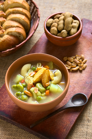 broad: Bowl of traditional Bolivian Sopa de Mani (peanut soup) made of meat, pasta, vegetables (pea, carrot, potato, broad bean, pepper, corn) and ground peanut, traditionally served with fried potatoes, photographed with natural light