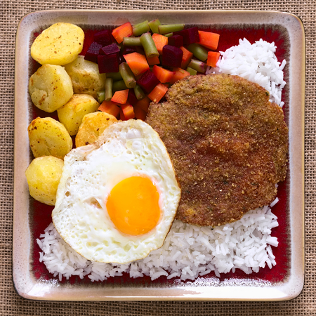 overhead shot: Overhead shot of traditional Bolivian dish called Silpancho, which is the name of the breaded flat, round piece of beef meat, served with fried egg, rice, fried potatoes and vegetables (carrot, bean, beetroot), photographed with natural light