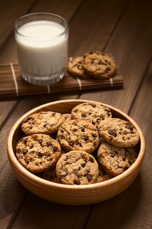 chocolate chips cookies: Chocolate chip cookies in wooden bowl with a glass of cold milk in the back, photographed on wood with natural light