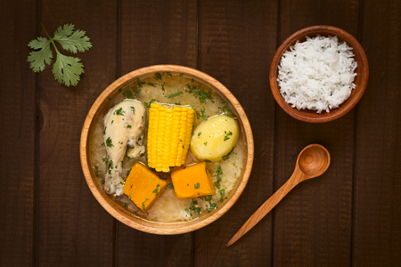 cazuela: Overhead shot of traditional Chilean Cazuela de Pollo (or Cazuela de Ave) soup made of chicken, sweetcorn, pumpkin and potato, seasoned with fresh coriander served in wooden bowl and rice on the side